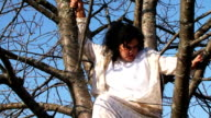 Crazy Dark-Haired Woman In Long White Nightie Sitting On Tree video