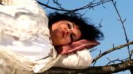 Crazy Dark-Haired Woman In Long White Nightie Sleeping On Tree video