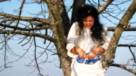 Crazy Dark-Haired Woman In Long White Nightie Throwing Pillow Feathers Around Sitting On Tree video