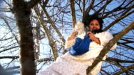 Crazy Dark-Haired Woman In Long White Nightie Throwing Pillow Feathers Sitting On Tree video