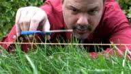 crazy man cutting grass with scissors video