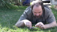 HD crazy man cutting the grass with  scissors video