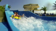 Crazy Water Race. Young mother with daughter fun slide down the water slide. video