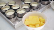 A cream cheese mixture being fill in a biscuit tart base tin. Making cheesecake video