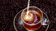 Cream pouring into coffee in slow motion video