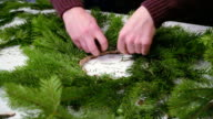 Creating a Christmas wreath with decorations. Close-up. video
