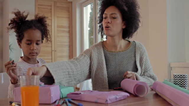 Creative African American mother and daughter wrapping gift boxes at home. video