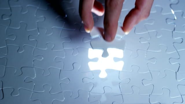 A creative completes the black or white light puzzle putting the last missing piece. Concept: cooperation, teamwork, creativity, and access solution. video
