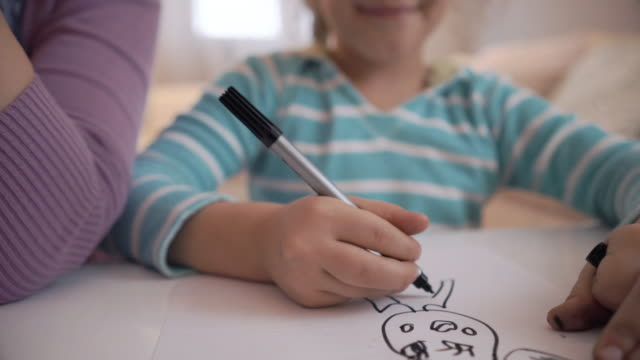 Creative little girl drawing on the paper and communicating with her mother. video