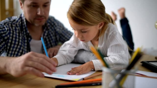 Creative little girl drawing with her father at home video