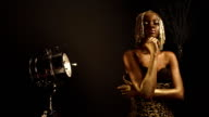 Creative surreal portrait of sexy african american female model with glossy golden makeup and headwear posing to the camera. Bronze bodypaint, black studio background. Vogue concept video