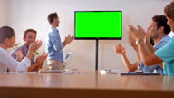 Creative team looking at television with green screen video