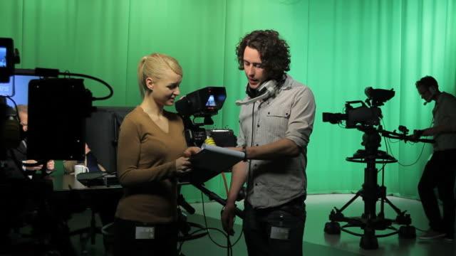 Crew in television studio discussing script video