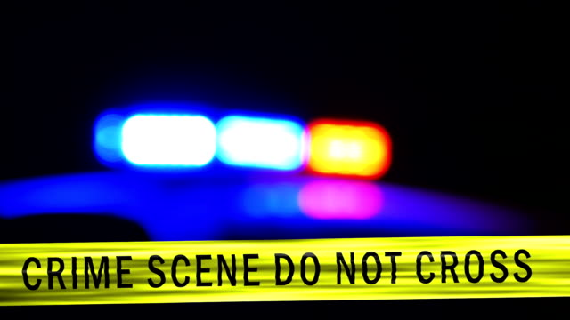 Crime scene tape with defocused flashing police car siren in background video