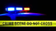 Crime scene tape with police car siren in background video