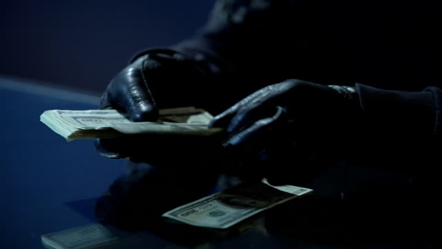 Criminal in black gloves counting bundle of money earned for committing crime video