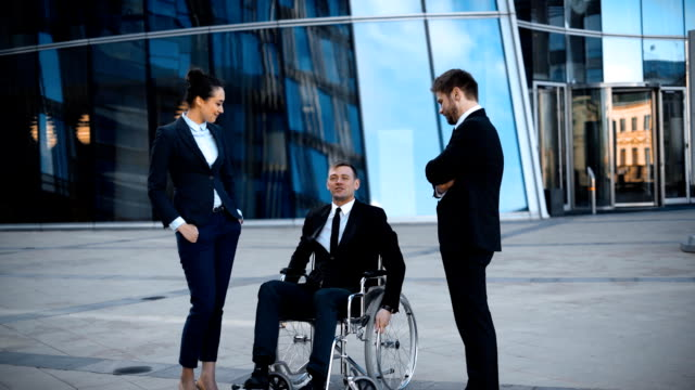 Cripple businessman in wheelchair and two his collegues has positive conversation video