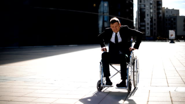Cripple businessman trying to get up from wheelchair outdoor video