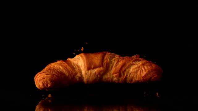 Croissant falling onto black surface video