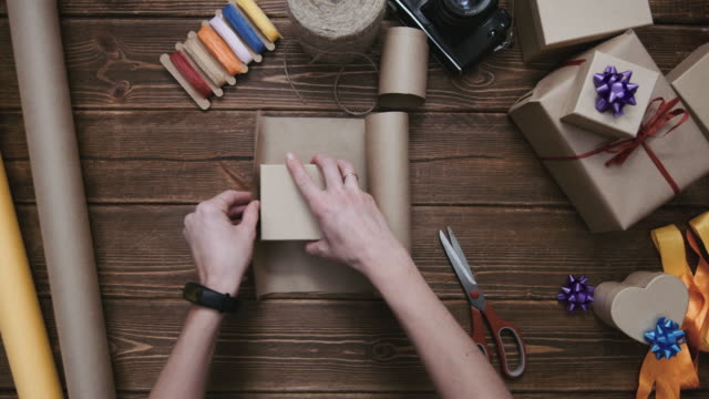 Crop hands cutting paper and wrapping present video