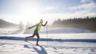 Cross country skier gliding on skiing track in winter landscape video