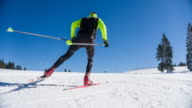 Cross country skier skate skiing uphill on a snowy landscape video