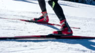 Cross country skiers feet skate skiing uphill video
