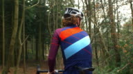 Cross-country cyclist resting and drinking on bike, back view, shot on R3D video