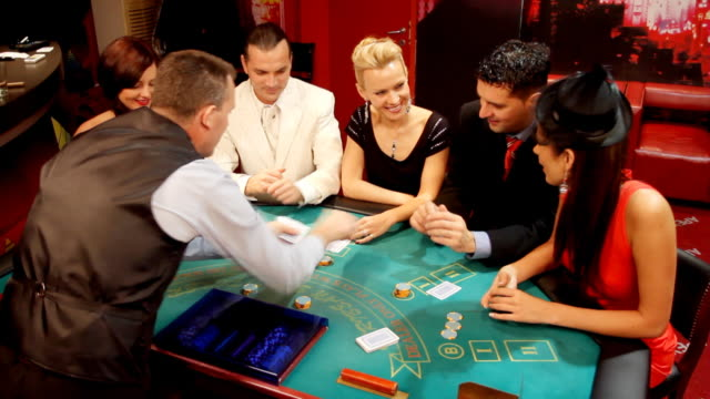 Croupier passing cards to blackjack gamblers in casino. video