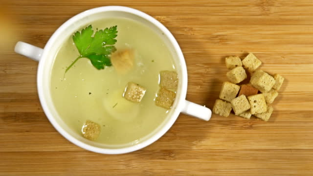 croutons falls into chicken soup Slow motion video