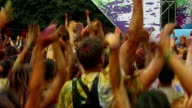 Crowd covered in colorful paint jumping to music at festival video