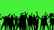 A crowd of dancing people, all in silhouette, on a greenscreen video