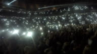 Crowd of fans waving phones in darkness. Lights sparkle during video