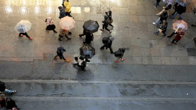 Crowd of people walking with umbrellas in rain on Istiklal Street, Beyoglu, Istanbul, Turkey. video