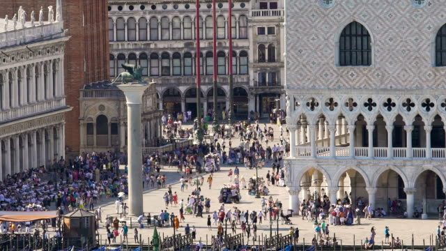 Crowded old square with colonnade buildings around and lion monument in middle video