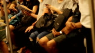 Crowded people in the mass public transportation using their phone while waiting video