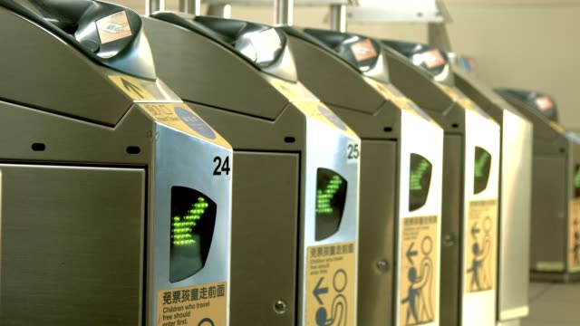 Crowds of people scanning subway passes and passing through ticket gate in Taipei downtown video