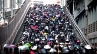 Crowed of people are riding scooters, Traffic on the bridge through city video