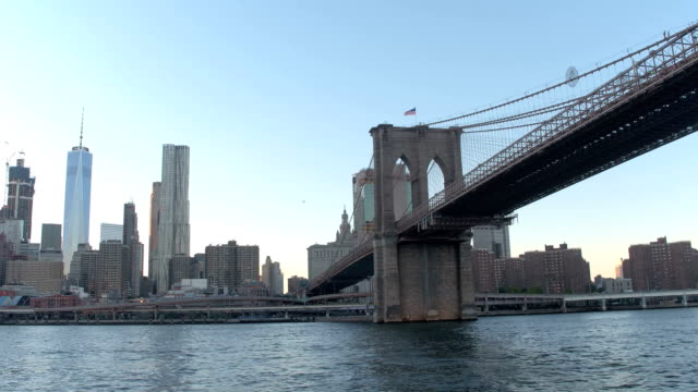 LOW ANGLE VIEW: Cruising along East River under famous Brooklyn Bridge at dawn video