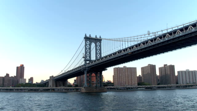 LOW ANGLE VIEW: Cruising along East River under famous Manhattan Bridge at dawn video