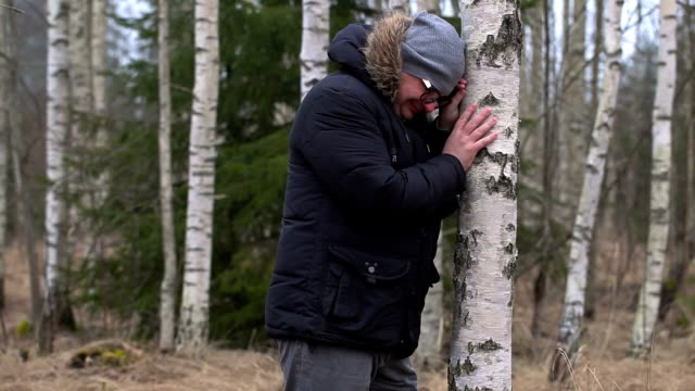 Crying man in birch grove in forest video