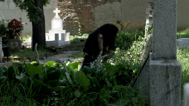 Crying woman in black mourning dress at the grave of beloved feeling desolation and sorrow video