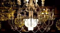 Crystal chandelier with yellow garlands on the dark background FullHD video