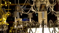 Crystal chandelier with yellow garlands on the dark background video