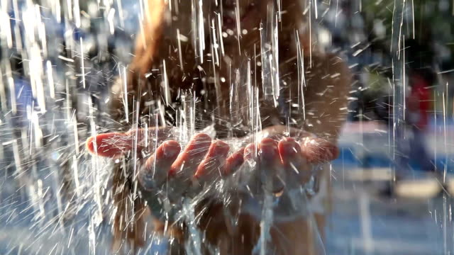 Crystal clear streams of water fall on the young woman's hands. video