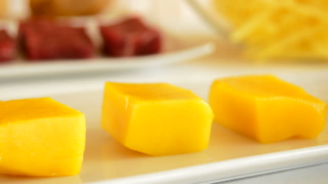 Cubes of mango fruit in a kitchen table with meat and others ingredients video