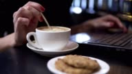 Cup of cappuccino and coockies. Woman muddling her cappuccino using spoon and working with laptop on the background. video