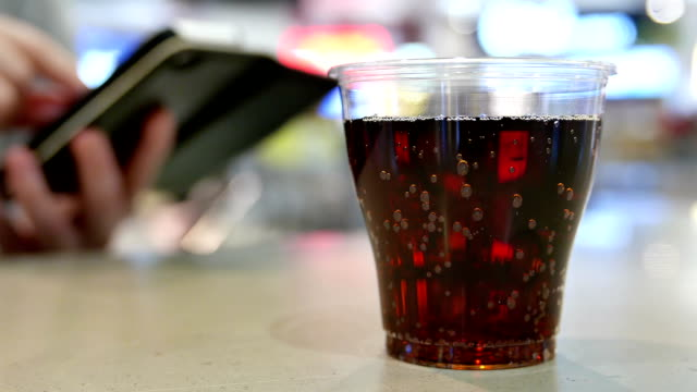 A cup of coca cola on table with woman reading message on iphone at food court inside shopping mall video