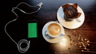 Cup of coffe with marshmellou, muffin and cellphone with green in cafe video