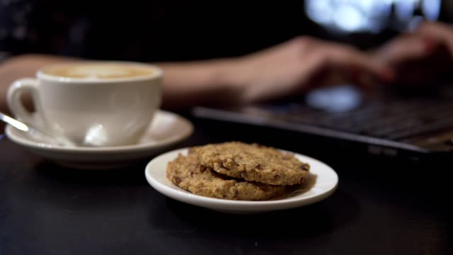 Cup of coffee and coockies. Woman working with laptop on the background video